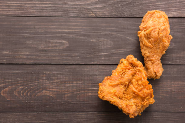 Fried chicken drumstick and chicken breast on the wooden backgro Fried chicken drumstick and chicken breast on the wooden background. Copyspace for your text. fried chicken stock pictures, royalty-free photos & images
