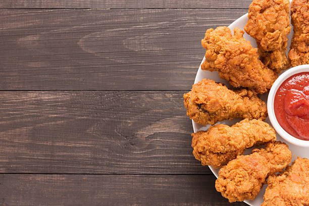 fried chicken drumstick and ketchup on wooden background fried chicken drumstick and ketchup on wooden background. fried chicken stock pictures, royalty-free photos & images