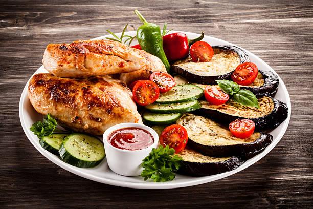 fried chicken fillets and vegetables on wooden background - schnitzel braten stock-fotos und bilder