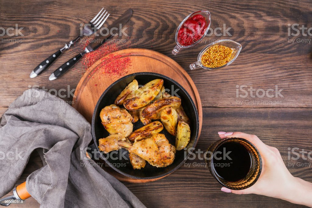 Fried chicken legs with fried potatoes in pan royalty-free stock photo