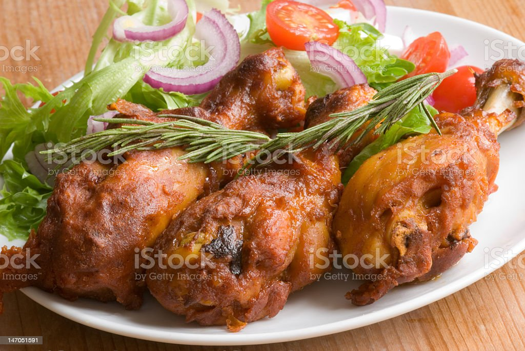 Fried chicken legs with salad on a plate royalty-free stock photo