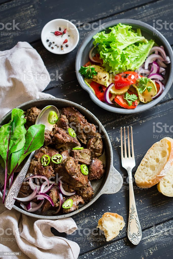 fried chicken liver and grilled vegetables stock photo