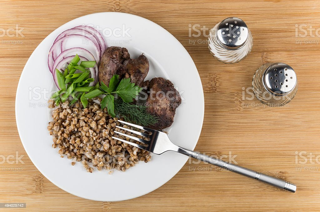 Fried chicken liver with buckwheat, onion, greens in plate stock photo