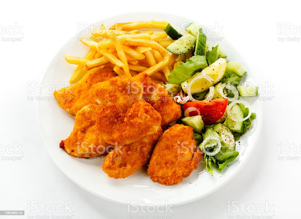 Fried chicken nuggets, French fries and vegetables stock photo