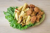 istock Fried chicken nuggets with french fries and lettuce. 1221057084