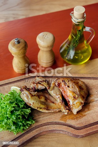 Fried Chicken Parts Is On Wooden Board Served With Salad Tomatoes Oil And Spices Stock Photo & More Pictures of Baked