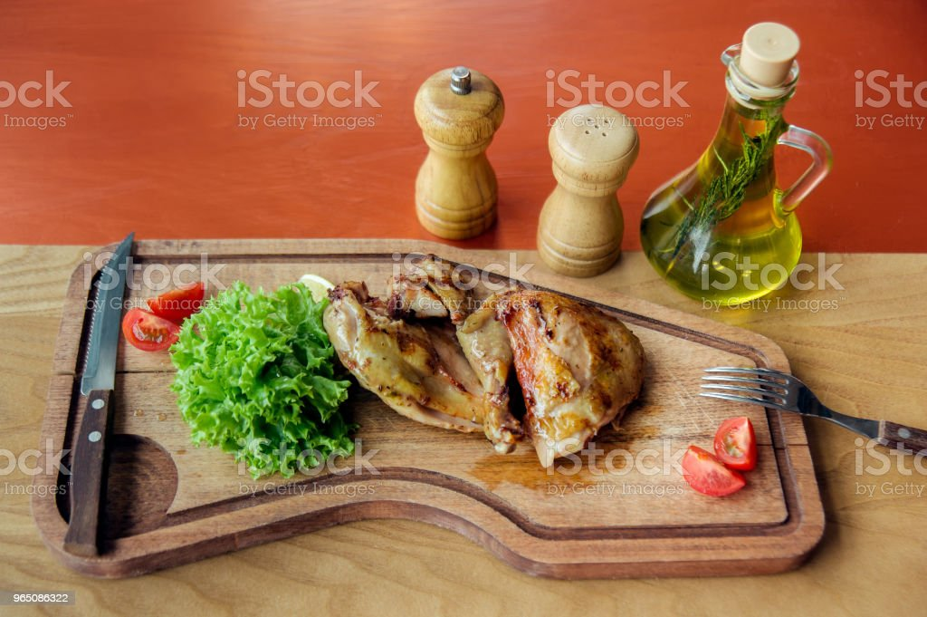 fried chicken parts is on wooden board served with salad, tomatoes, oil and spices zbiór zdjęć royalty-free