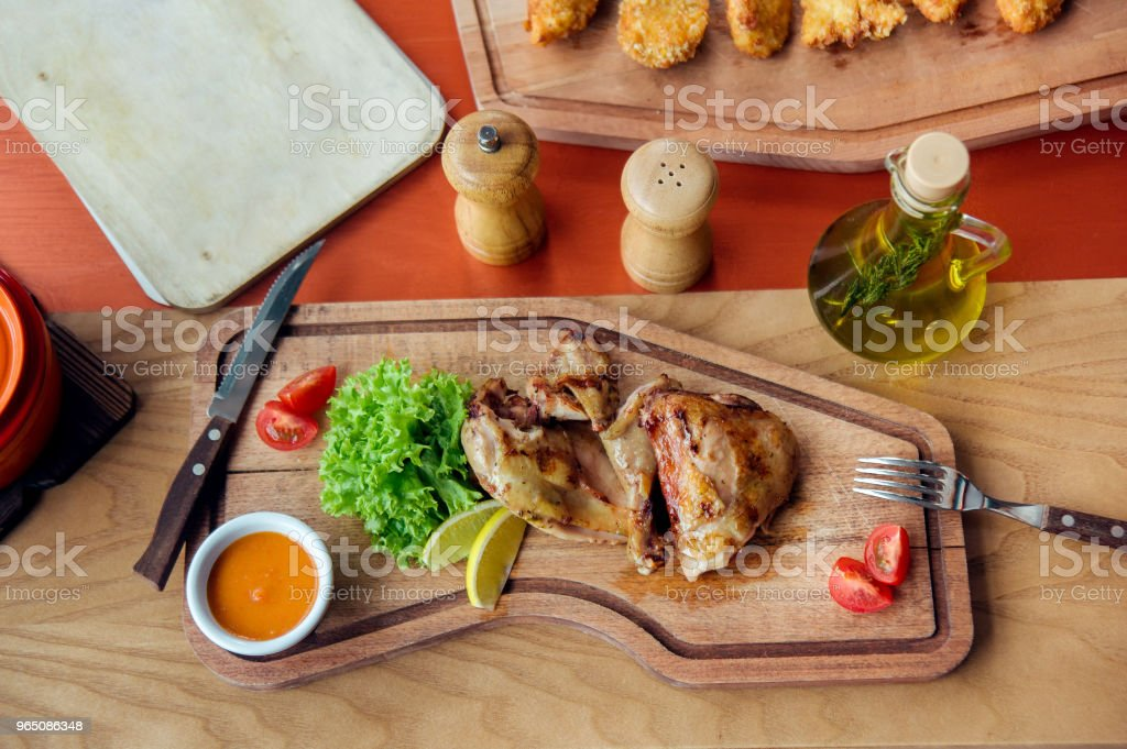 fried chicken parts is on wooden board served with salad, tomatoes, oil and spices royalty-free stock photo