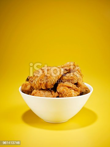 Bowl full of fried chicken on yellow background