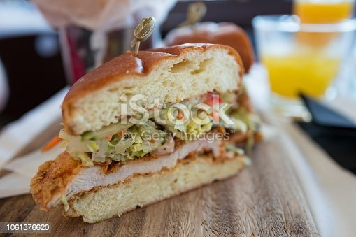 Close-up of cut half of a fried chicken sandwich with coleslaw on a wooden serving board, October 20, 2018. (Photo by Smith Collection/Gado/Getty Images)