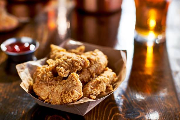 fried chicken tenders in paper basket stock photo