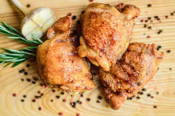 smażone uda kurczaka na drewnianej desce - kurczak zdjęcia i obrazy z banku zdjęć