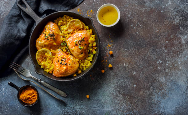 Fried chicken thighs with rice and chickpeas stock photo