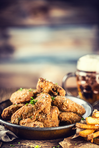 Fried Chicken Wings Fries And Draft Beer On Table In Pub ...