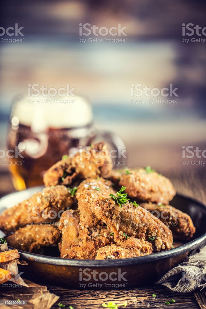 Fried chicken wings fries and draft beer on table in pub or restaurant. stock photo