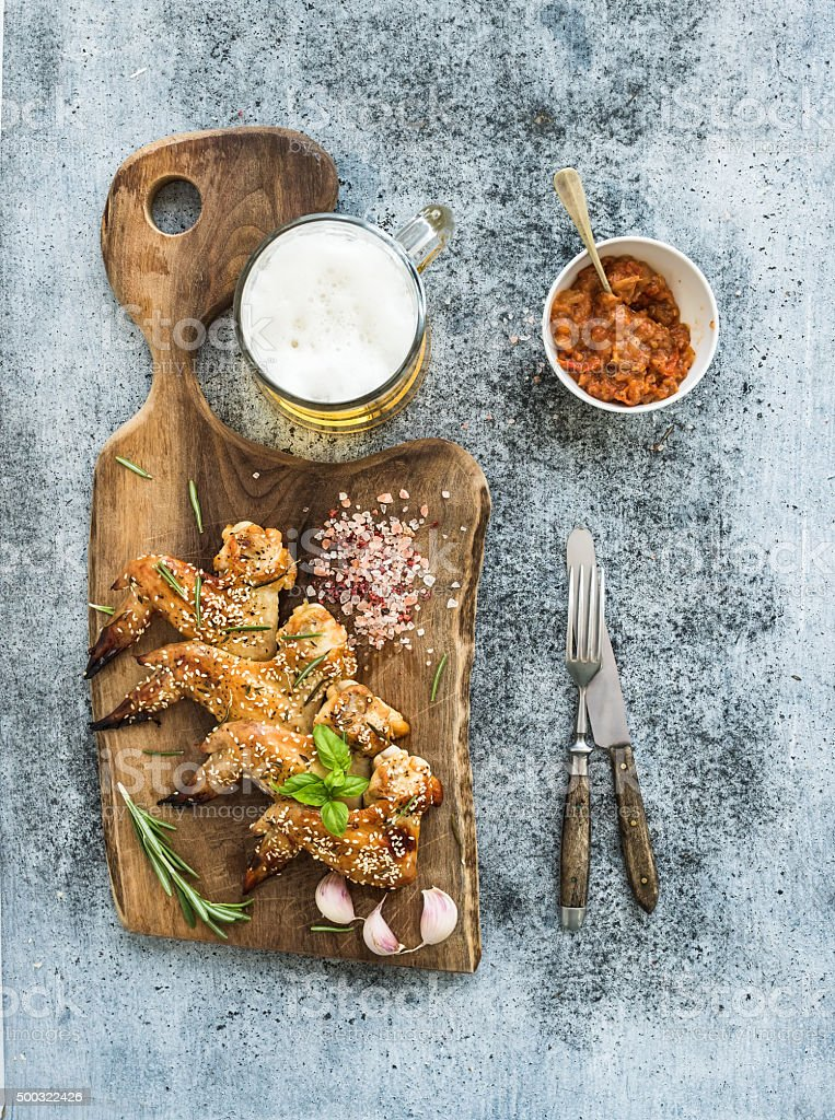 Fried chicken wings on rustic serving board, spicy tomato sauce stock photo