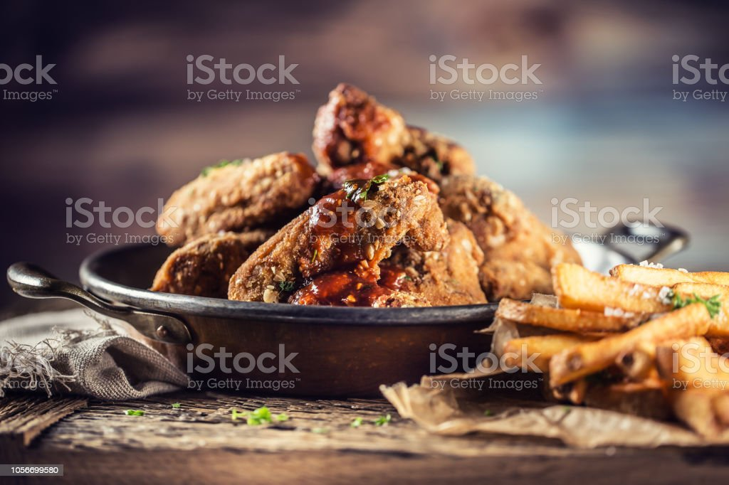 Fried chicken wings with fries on table in pub or restaurant. stock photo