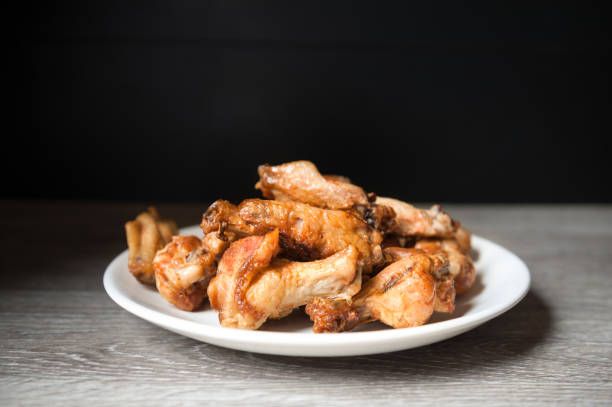 fried chiken wings in the plate on dark stock photo
