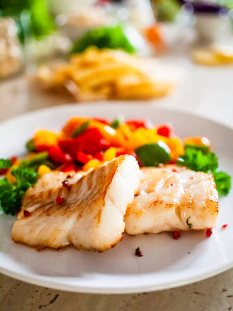 Fried cod fillet and vegetables stock photo