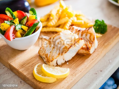 Fish dish - fried cod loin with French fries and vegetables