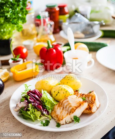 istock Fried cod fillet with potatoes and vegetables 1074230680