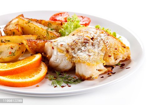 Fried cod fillet with baked potatoes and vegetables