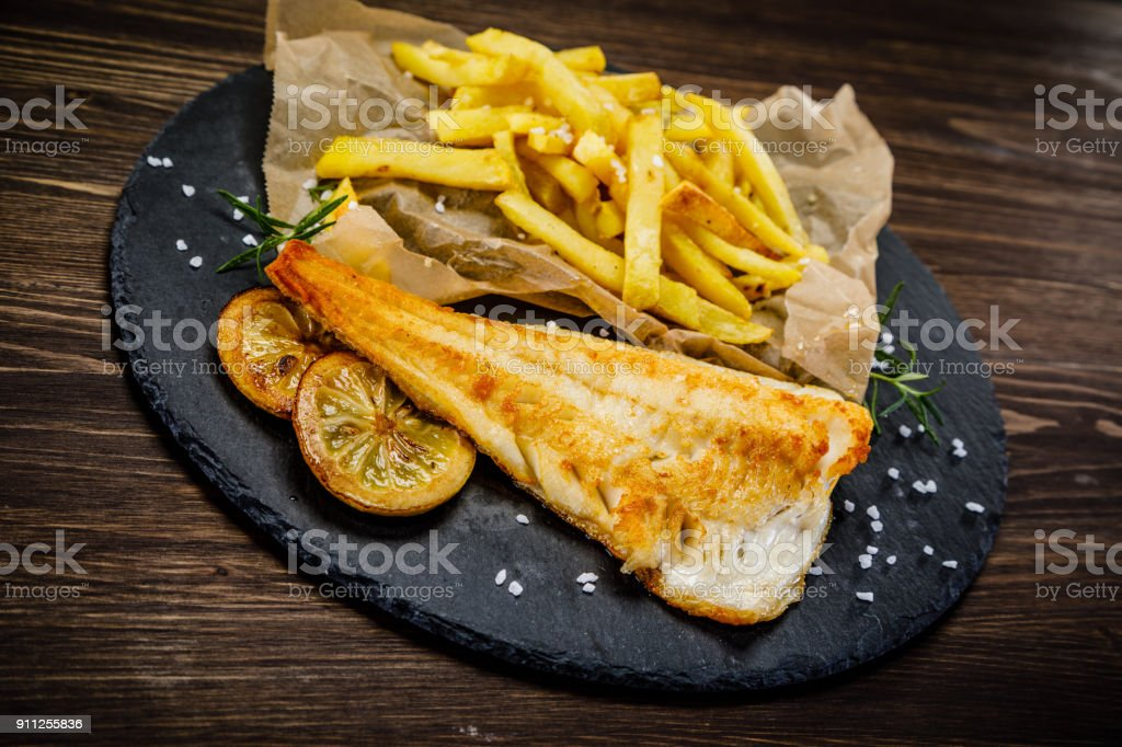 Fried cod fillet with potatoes and vegetables stock photo