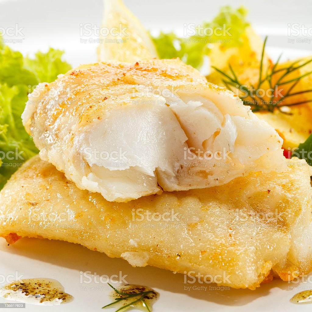Fried cod fillets with rosemary and lettuce on the side stock photo