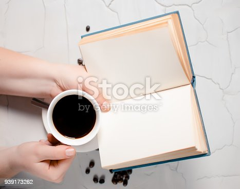Fried coffee beans and in the hands of the girl a cup of hot delicious coffee and an open book on a gray background. Place for text. Concept of coffee beans