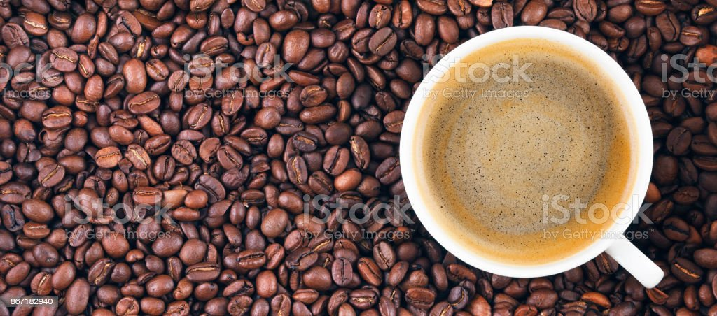 Fried coffee beans. Coffee mug on the background of coffee beans. stock photo