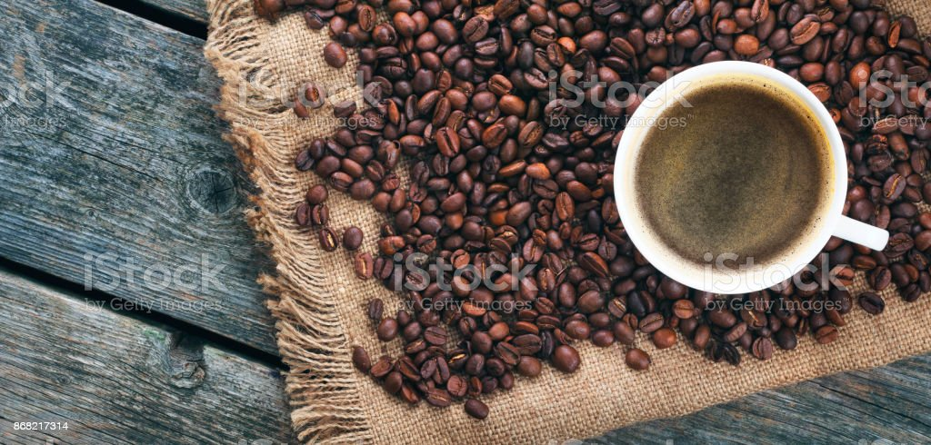 Fried coffee beans. Coffee mug on the background of coffee beans. Panorama, banner. stock photo