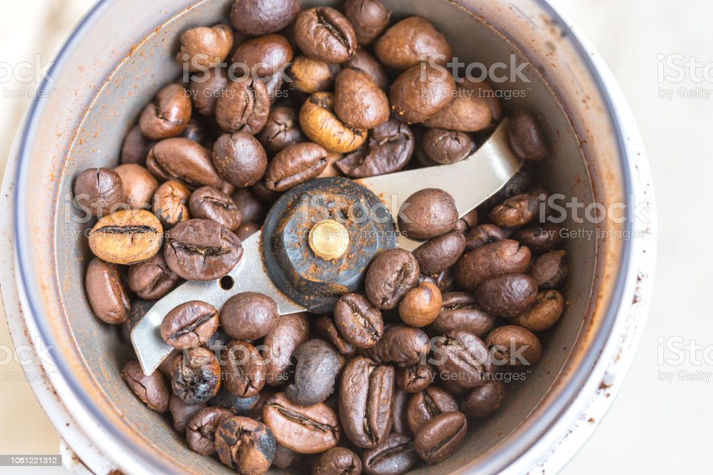 Fried coffee beans in a coffee grinder. Macro stock photo