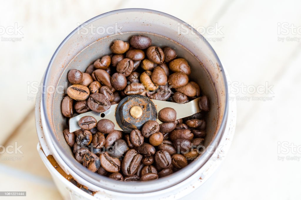 Fried coffee beans in a coffee grinder. Macro Vintage toning stock photo