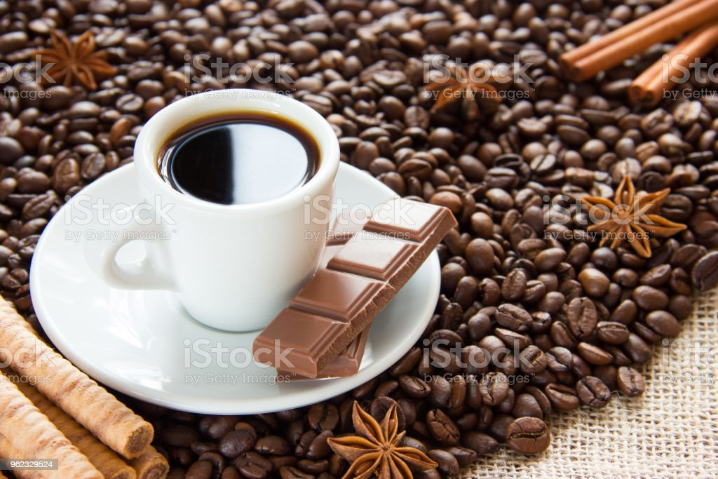 fried coffee beans with a cup on a saucer with an espresso drink with cinnamon and anise and milk chocolate stock photo