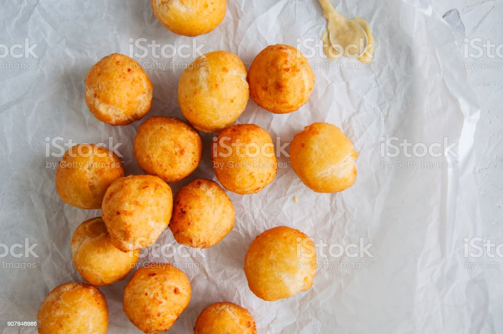 Fried cottage cheese doughnuts with vanilla sauce on a baking paper. Top view. stock photo