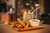 Fried crispy chicken nuggets served with mustard sauce and french fries