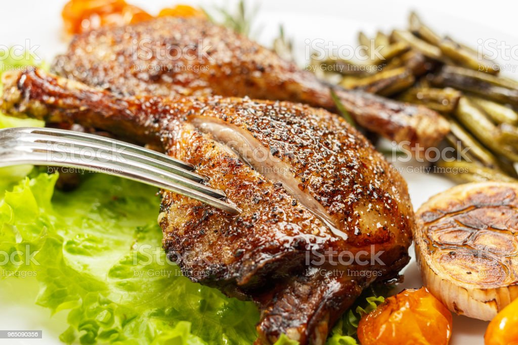 Fried duck legs, ready to serve. The finished dish for use in the restaurant menu. royalty-free stock photo
