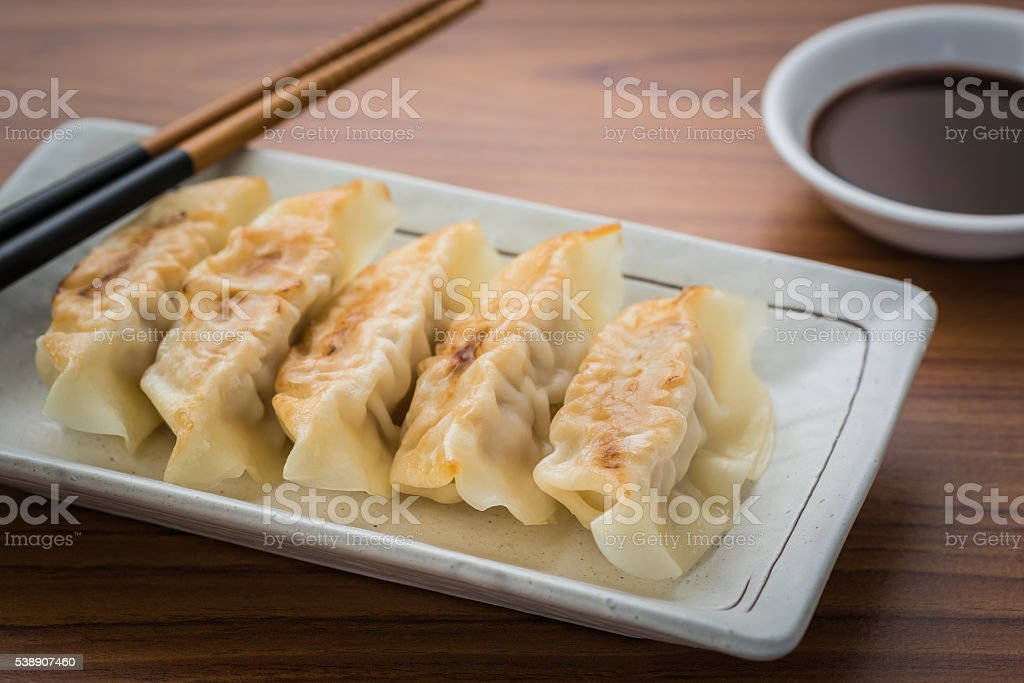 Fried dumplings on plate and soy sauce stock photo