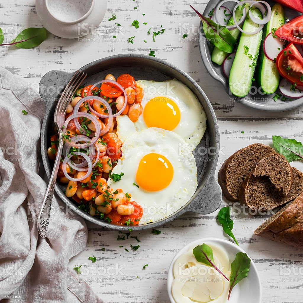 Huevo frito, frijoles en salsa de tomate y pepino y tomates foto de stock libre de derechos