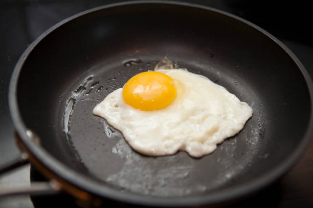 Fried egg cooking in frying pan stock photo