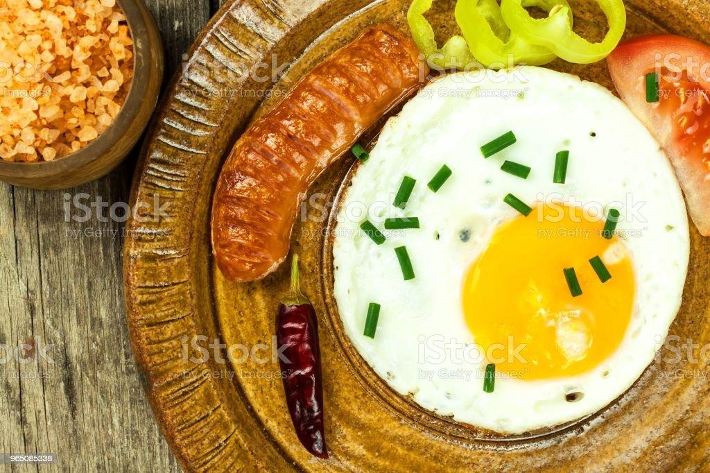 Fried egg for breakfast. Diet food. Food preparation. Fried egg on a wooden table. zbiór zdjęć royalty-free