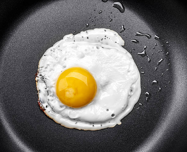 fried egg in a frying pan - fried egg stock photos and pictures