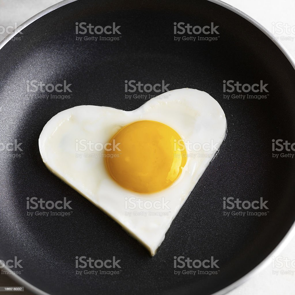 Fried egg like heart on frying pan. royalty-free stock photo