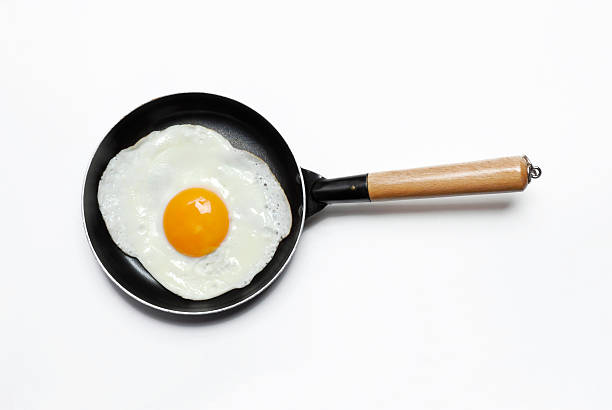 fried egg on a pan on cenital view on white background. - fried egg stock photos and pictures