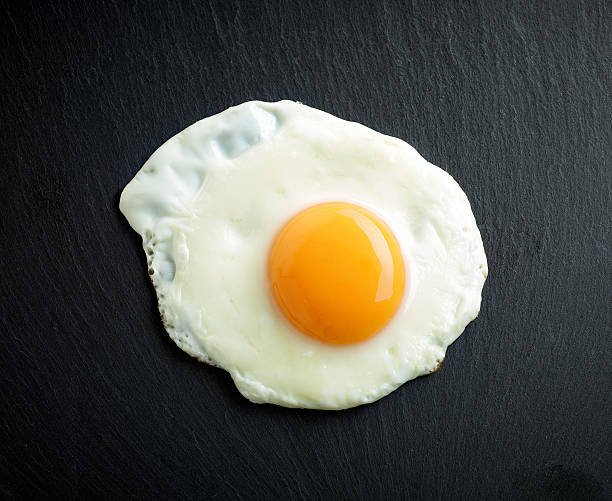 fried egg on black background - fried egg stock photos and pictures