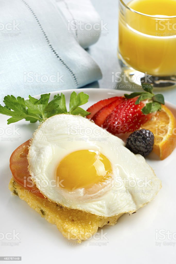 Fried egg on grits - stock image stock photo