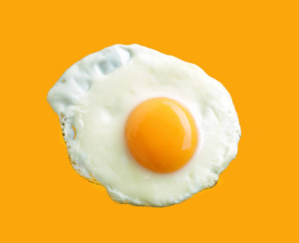 fried egg on yellow background - fried egg stock photos and pictures