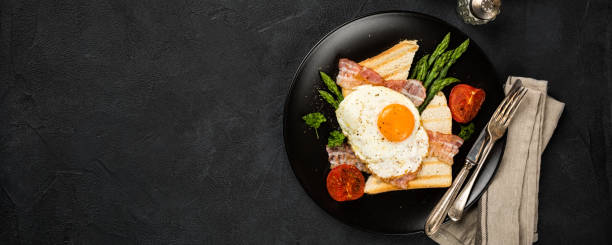 Fried egg with bread toast and asparagus stock photo