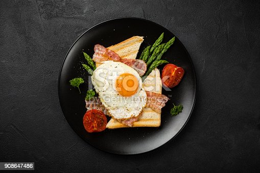 istock Fried egg with bread toast and asparagus 908647486