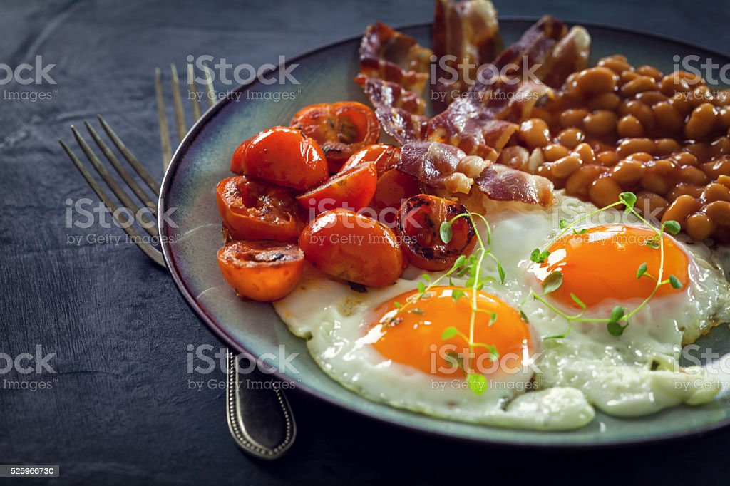 Fried eggs, bacon beans and cherry tomatoes stock photo
